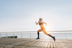 Muchacha atlética hermosa joven con el pelo rubio largo en la ropa negra que corre en la salida del sol sobre el mar Imágenes de archivo libres de regalías
