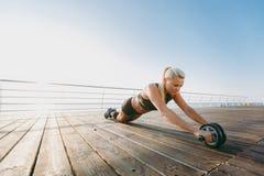 Muchacha atlética hermosa joven con el pelo rubio largo en ropa negra que entrena con pesas de gimnasia en la salida del sol sobr Imagen de archivo libre de regalías