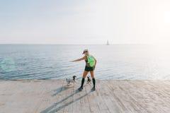 Muchacha atlética hermosa joven con el pelo rubio largo en ropa negra y dos de sus perros que hacen deportes en la salida del sol Imagen de archivo