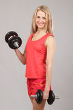 Muchacha atlética hermosa joven que lleva a cabo pesas de gimnasia Fotos de archivo libres de regalías
