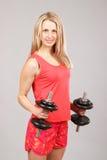Muchacha atlética hermosa joven que lleva a cabo pesas de gimnasia Fotografía de archivo