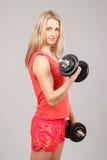Muchacha atlética hermosa joven que lleva a cabo pesas de gimnasia Foto de archivo