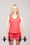 Muchacha atlética hermosa joven que lleva a cabo pesas de gimnasia Fotografía de archivo libre de regalías