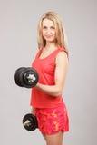 Muchacha atlética hermosa joven que lleva a cabo pesas de gimnasia Foto de archivo libre de regalías