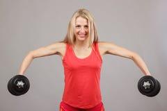Muchacha atlética hermosa joven que lleva a cabo pesas de gimnasia Imagen de archivo