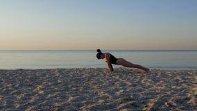 Muchacha atlética que hace algunos ejercicios de la yoga en la arena contra el mar y el cielo en la salida del sol forma de vida