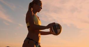 Muchacha atlética que juega saltos del voleibol de playa en el aire y las huelgas la bola sobre la red en una tarde hermosa del v almacen de video