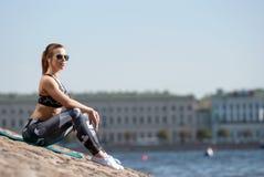 Muchacha atlética que se relaja después de un entrenamiento en la costa urbana Fotos de archivo