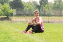 Muchacha atlética sonriente que usa los auriculares del smartphone que escuchan Foto de archivo libre de regalías