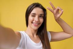 Muchacha atractiva agradable que hace el selfie en estudio y la risa Mujer joven apuesta con el pelo marrón que toma la imagen imagen de archivo