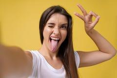 Muchacha atractiva agradable que hace el selfie en estudio y la risa Mujer joven apuesta con el pelo marrón que toma la imagen fotos de archivo