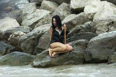 Muchacha atractiva al día de la lluvia en las rocas del océano Fotografía de archivo