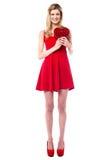 Muchacha atractiva alta que sostiene el regalo en forma de corazón Imagen de archivo libre de regalías