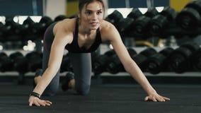 Muchacha atractiva apta que hace el tablón en gimnasio metrajes