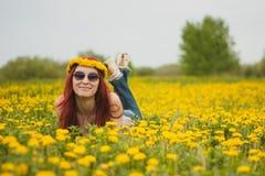 Muchacha atractiva atractiva de moda joven con una guirnalda en su cabeza y vidrios que mienten en un margarita-prado en soleado Fotos de archivo libres de regalías