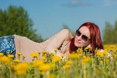Muchacha atractiva atractiva de moda joven en los vidrios que mienten en un margarita-prado en el día de verano soleado Imagen de archivo