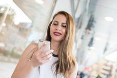 Muchacha atractiva cheking el teléfono elegante mientras que camina Imagenes de archivo
