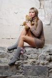 Muchacha atractiva con el oso de peluche que se sienta en la pared Fotografía de archivo libre de regalías