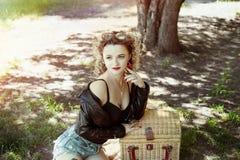 Muchacha atractiva con el pelo con curvas y las gafas de sol con el bolso de la comida campestre foto de archivo