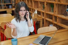 Muchacha atractiva con el pelo largo y la piel blanca pura que se sientan en una tabla en un café que habla en el teléfono Imagen de archivo