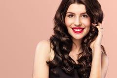 Muchacha atractiva con el pelo ondulado largo y brillante Modelo hermoso, peinado rizado en fondo anaranjado Fotos de archivo libres de regalías