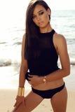 Muchacha atractiva con el pelo oscuro y la piel bronceada que presentan en la playa Imagen de archivo