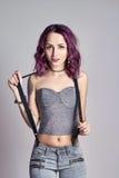 Muchacha atractiva con el pelo púrpura y un tatuaje en el cuerpo que presenta en fondo gris Mujer perfecta en vaqueros grises y u Foto de archivo