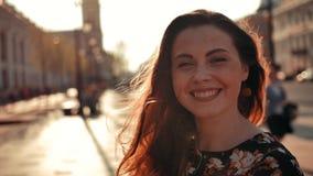 Muchacha atractiva con el pelo rojo largo que da vuelta alrededor y que sonríe en la cámara al aire libre almacen de metraje de vídeo