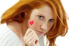 Muchacha atractiva con el pelo rojo que lleva a cabo un corazón Foto de archivo
