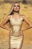Muchacha atractiva con el pelo rubio largo en el vestido del oro que presenta en la playa Imágenes de archivo libres de regalías