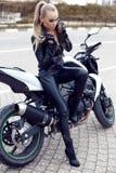 Muchacha atractiva con el pelo rubio largo en la chaqueta de cuero, presentando en la moto imagen de archivo