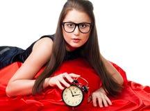 Muchacha atractiva con el reloj de alarma Foto de archivo libre de regalías
