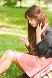Muchacha atractiva con el teléfono en parque Fotos de archivo libres de regalías