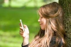 Muchacha atractiva con el teléfono en parque Foto de archivo libre de regalías
