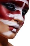 Muchacha atractiva con la pintura roja en su cara Foto de archivo libre de regalías