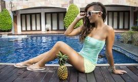 Muchacha atractiva con las gafas de sol que se sientan cerca de piscina Imágenes de archivo libres de regalías