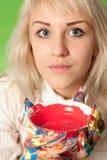 Muchacha atractiva con las manos coloridas a la taza de pintura roja Fotos de archivo