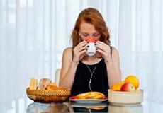 Muchacha atractiva con las pecas que bebe de la taza Imagen de archivo