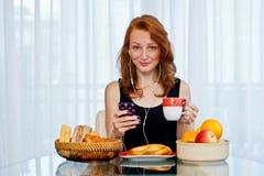 Muchacha atractiva con las pecas que come el desayuno Fotografía de archivo libre de regalías