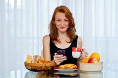 Muchacha atractiva con las pecas que come el desayuno Fotografía de archivo