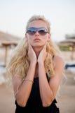 Muchacha atractiva con los vidrios en una playa Imagen de archivo libre de regalías
