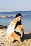 Muchacha atractiva con su perro que lleva la ropa caliente Imágenes de archivo libres de regalías