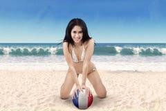 Muchacha atractiva con un balón de fútbol en la playa Imagen de archivo