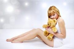 Muchacha atractiva con un oso de peluche Foto de archivo libre de regalías
