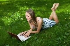 Muchacha atractiva con una computadora portátil en el parque Imagen de archivo libre de regalías