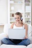 Muchacha atractiva con una computadora portátil Imagenes de archivo