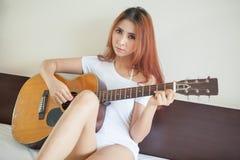 Muchacha atractiva con una guitarra Imagen de archivo