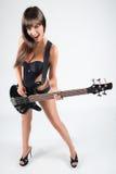 Muchacha atractiva con una guitarra. En un traje de baño negro, Foto de archivo