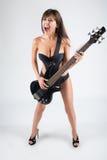Muchacha atractiva con una guitarra. En un traje de baño negro, Imágenes de archivo libres de regalías