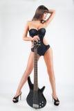 Muchacha atractiva con una guitarra. En un traje de baño negro, Imagen de archivo libre de regalías